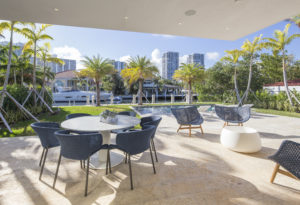 Golden Beach house modern luxury high-end miami contractor builder coral stone pool deck exterior outdoors covered terrace table dining view waterfront landscape