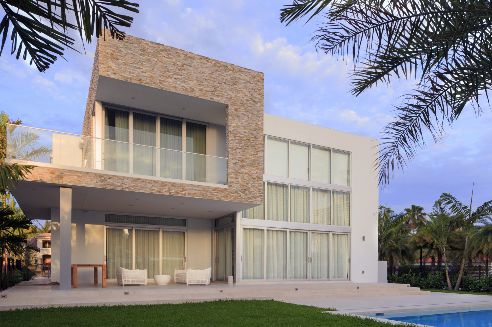 House construction miami florida custom builder contractor luxury modern residential back pool yard landscape grass windows