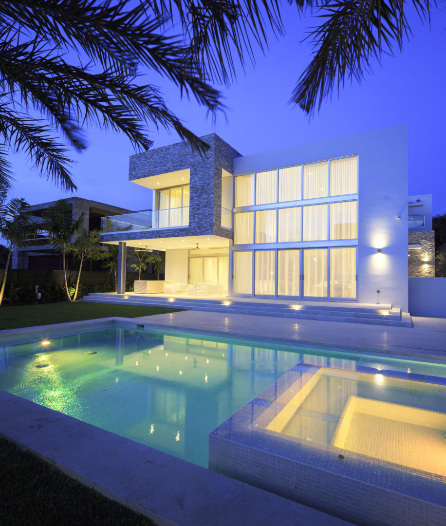 House construction miami florida custom builder contractor luxury modern residential back pool yard landscape grass windows lighting
